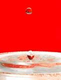 liten droppe som faller över rött vatten Arkivbilder