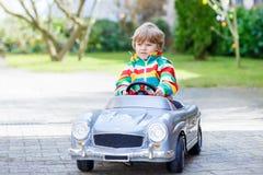 Liten förskole- pojke som kör gammal tappning för stor leksak Royaltyfri Foto