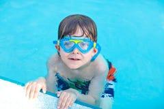 Liten förskole- ungepojke som gör badkonkurrenssporten Unge med att simma skyddsglasögon som når kanten av pölen barn arkivfoto