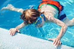 Liten förskole- ungepojke som gör badkonkurrenssporten Unge med att simma skyddsglasögon som når kanten av pölen barn royaltyfri foto