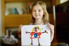 Liten förskolebarnflicka som visar hennes bild arkivfoto