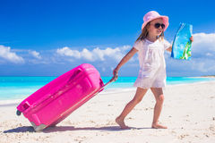 Liten förtjusande flicka med den stora färgrika resväskan och en översikt i händer på den tropiska stranden Arkivbilder
