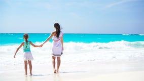 Liten förtjusande flicka och barnmoder på den tropiska stranden Familjen på karibisk semester tycker om havssikten lager videofilmer