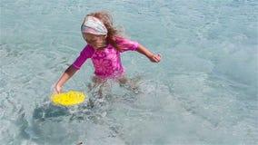 Liten förtjusande flicka som spelar frisbeen under tropisk semester Ungen har gyckel med strandleksaken i grunt vatten stock video