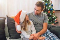 Liten familj som tillsammans spenderar tid De sitter på soffan och ser de Flickan bär julhatten Den unga mannen är in fotografering för bildbyråer