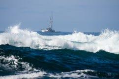 Liten fiskebåt med bränning Fotografering för Bildbyråer