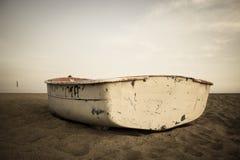 Liten fiskebåt på stranden och himlen Arkivfoto