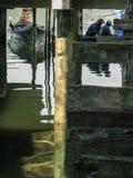 Liten fiskebåt som förtöjas under bron på havet royaltyfri foto