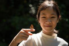 Liten fjäril på fingret av en asiatisk flicka, gullig flickalearni arkivbilder
