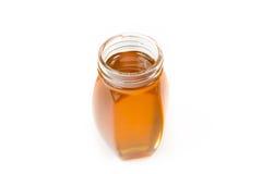 Liten flaska som fylls med honung Arkivfoto