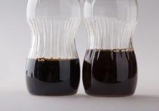 Liten flaska två med svart flytande Arkivbilder