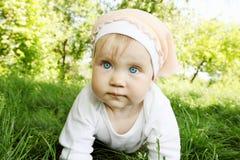 Flickan är krypanden på gräs Arkivbild