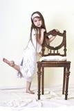 Liten flicka är nära stolen Arkivfoto