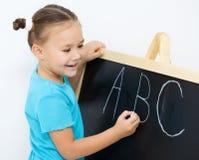 Liten flicka är writingbokstäver på en blackboard royaltyfri foto