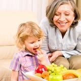 Liten flicka äter aprikosfrukt med farmodern royaltyfria bilder