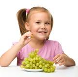 Liten flicka äter druvor fotografering för bildbyråer