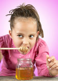 Liten flicka äter honung royaltyfri bild