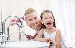 Liten flicka brushes tänder med henne modern royaltyfri bild
