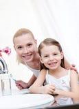Liten flicka brushes tänder med henne mumen arkivbild