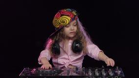 Liten flicka dj i det ljusa locket som spelar på vinyl studio arkivfilmer