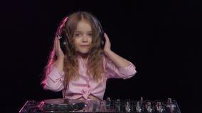 Liten flicka dj i hörlurar som spelar på vinyl Svart bakgrund arkivfilmer