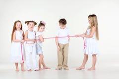 Liten flicka drar över rep, och pojken ser repet Royaltyfri Foto