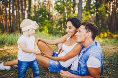 Liten flicka ett år på bakgrunden av föräldrar som vilar som ligger på gräs som lär att gå på naturen i parkera Första stegnollan Arkivbild