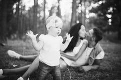 Liten flicka ett år på bakgrunden av föräldrar som vilar som ligger på gräs som lär att gå på naturen i parkera Första stegnollan Arkivbilder