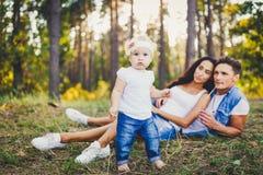 Liten flicka ett år på bakgrunden av föräldrar som vilar som ligger på gräs som lär att gå på naturen i parkera Första stegnollan Royaltyfri Foto