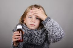 Liten flicka för blont hår som rymmer hostasirap i en hand sjukt barn Begrepp för hälsovård för barnvinterinfluensa arkivfoto