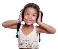 Liten flicka för gullig afrikansk amerikan som lyssnar till musik på radion Royaltyfria Foton