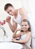 Liten flicka gör ren tänder med henne fadern arkivfoton