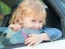 liten flicka 3 gamla år, i bilen Arkivfoton