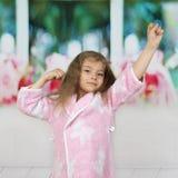 Liten flicka i ämbetsdräktelasticiteter i morgonen royaltyfri fotografi