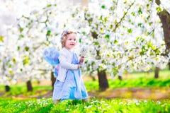 Liten flicka i äppleträdgård Arkivbild