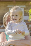 Liten flicka i armarna av en kvinna Arkivfoto