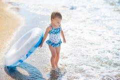 Liten flicka i baddräkt med simningcirkeln som är klar att gå in i havet på den tidiga solnedgången blåa pojkeskrivbordflickor se royaltyfri bild