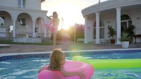 Liten flicka i baddräktdans av simbassängen, sött barn i uppblåsbart cirkelbad i pöl i solljus, stock video