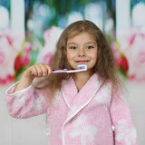 Liten flicka i badrocken som går att borsta tänder fotografering för bildbyråer