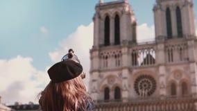 Liten flicka i basker genom att använda mynt-fungeringsteleskopet långsam rörelse dame de notre paris Stationär kikare semester stock video