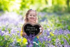 Liten flicka i bluebelssblommor Royaltyfria Foton