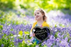 Liten flicka i bluebelssblommor fotografering för bildbyråer