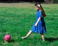 Liten flicka i den bl?a kl?nningen som sparkar fotbollbollen p? gr?nt gr?s arkivbild
