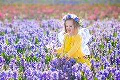 Liten flicka i den felika dräkten som spelar i blommafält Arkivfoto