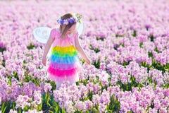 Liten flicka i den felika dräkten som spelar i blommafält Royaltyfri Bild