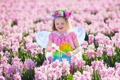 Liten flicka i den felika dräkten som spelar i blommafält Royaltyfri Fotografi