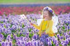 Liten flicka i den felika dräkten som spelar i blommafält Arkivbild