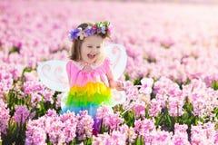 Liten flicka i den felika dräkten som spelar i blommafält Arkivbilder