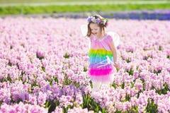 Liten flicka i den felika dräkten som spelar i blommafält Royaltyfri Foto