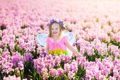 Liten flicka i den felika dräkten som spelar i blommafält Arkivfoton
